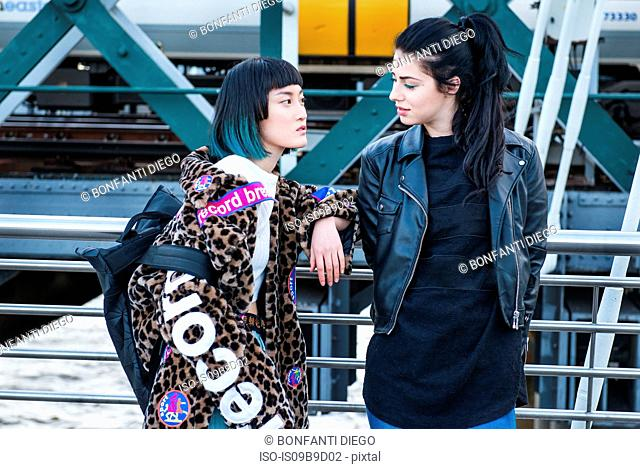 Two young stylish women leaning against handrail on millennium footbridge, London, UK
