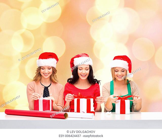 christmas, holidays, celebration, decoration and people concept - smiling women in santa helper hats with decorating paper and gift boxes over beige lights...
