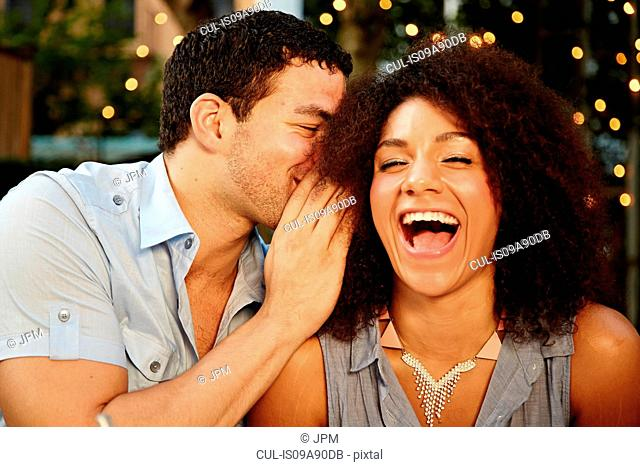 Young man whispering to laughing woman at garden party