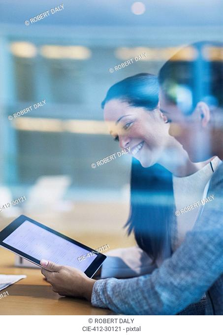 Smiling businesswomen using digital tablet in office