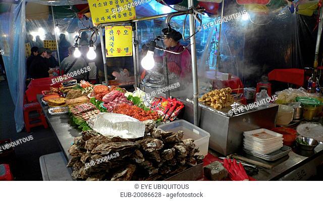 Namdaemun market, street restaurant, stacks of meat and fish waiting to be dooked, oysters in foreground