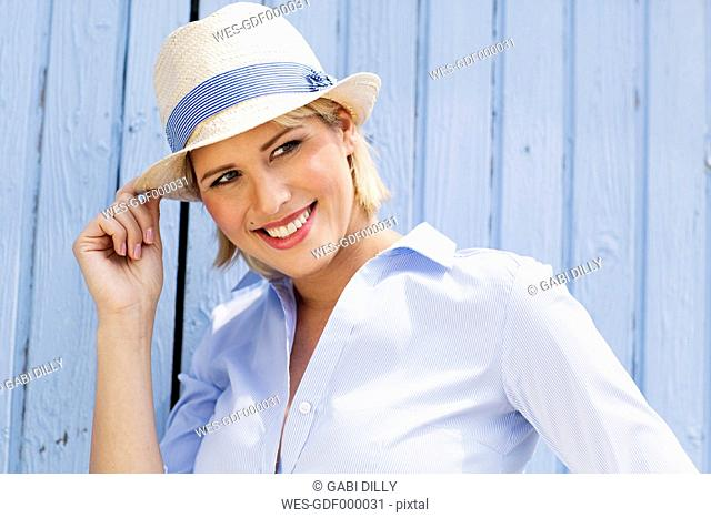 Germany, North Rhine Westphalia, Young woman looking away, smiling, close up