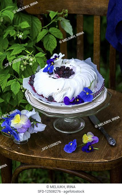 A festive pavlova with berries and pansies on a vintage chair