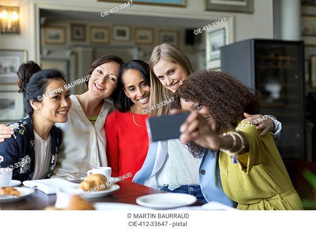 Smiling women friends taking selfie at restaurant table