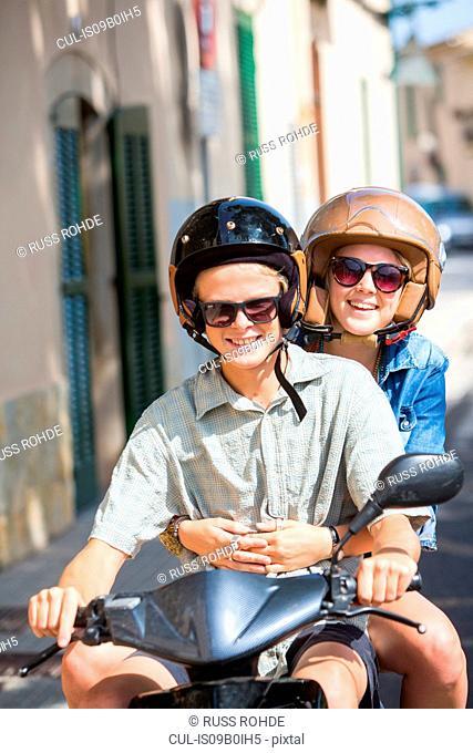 Young couple riding moped through village, Majorca, Spain