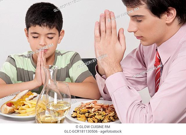 Man and his son praying before lunch