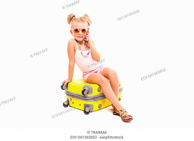Isolated on white, attractive young caucasian blonde girl in white shirt, pink shorts, sunglasses and sandals sit on the yellow suitcase, look at camera