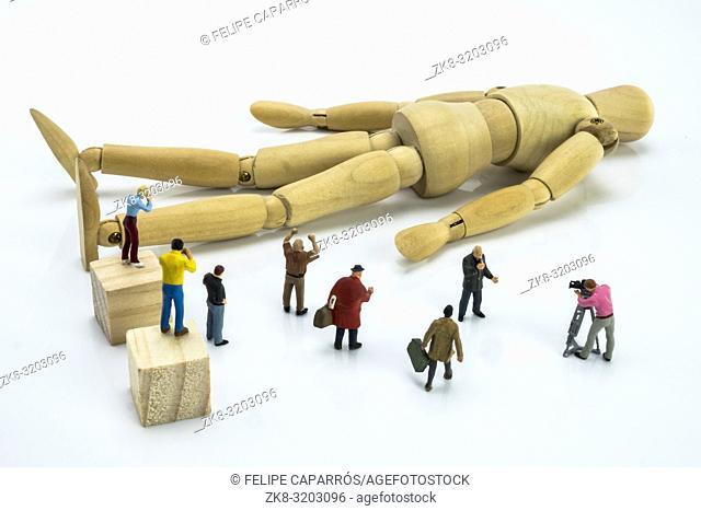 Miniature figures surrounding wood doll, conceptual image