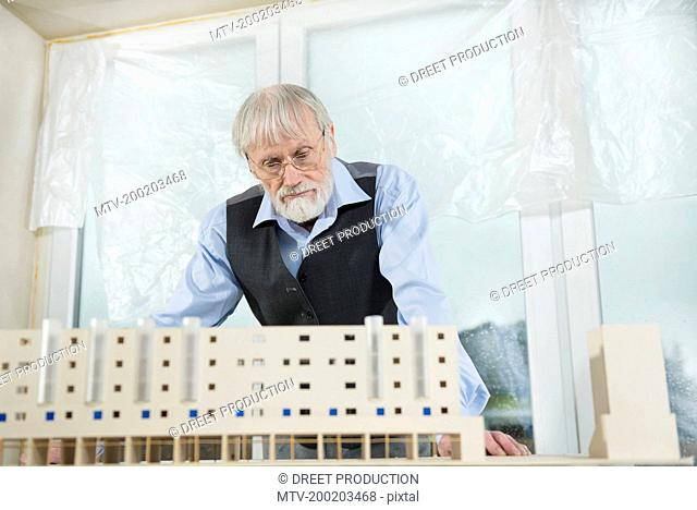 Architect looking at architectural model