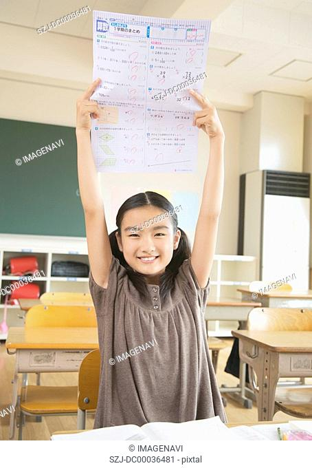 Elementary school girl showing test paper