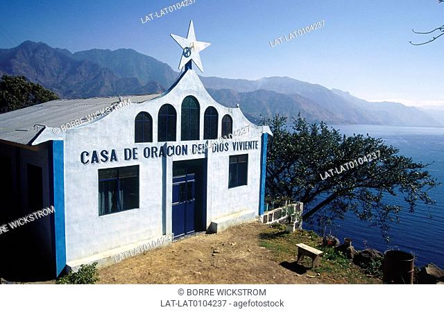 Church. Sign in Spanish. White stone wall. Blue sky. View to lake