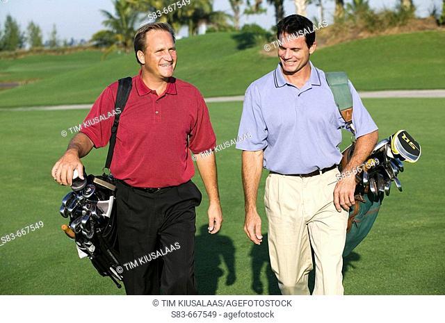 Golfers walking down fairway