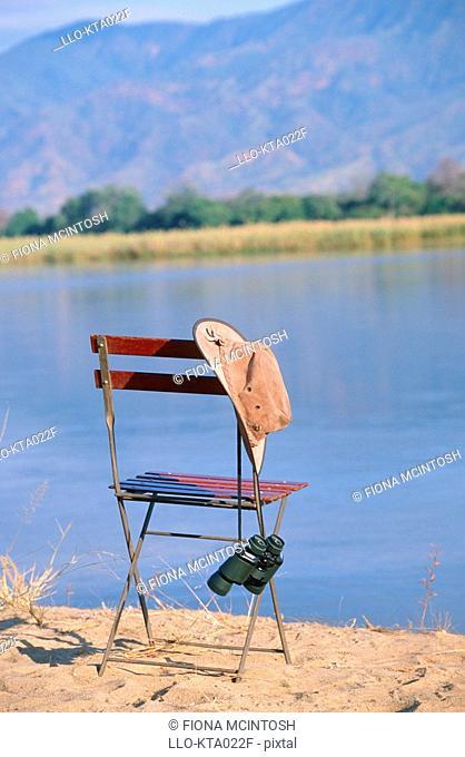 Chair, Hat and Binoculars on a Riverbank  Zambezi River, Zambia