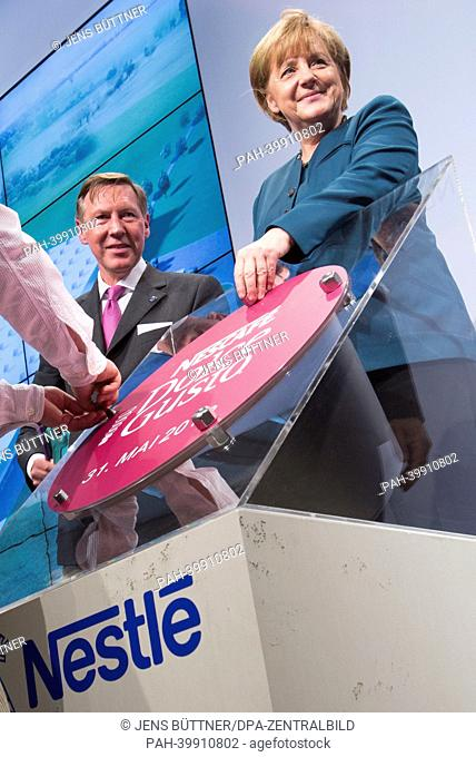 German Chancellor Angela Merkel (R-L) and CEOof Nestlé Germany Gerhard Berssenbruegge attend the cornerstone laying ceremony for the new Nestlé coffee capsule...