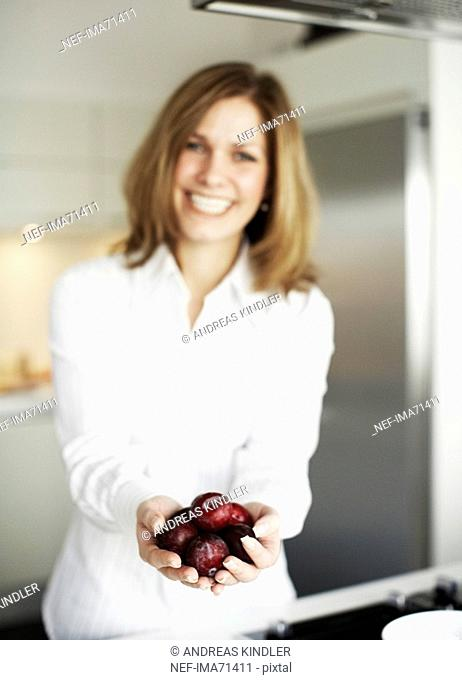 A smiling woman holding plums Sweden