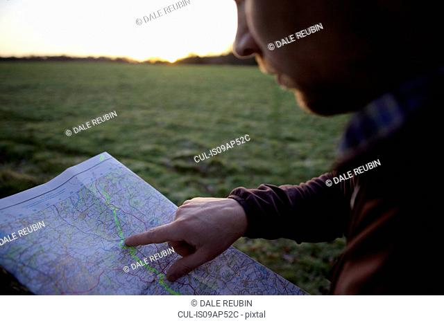 Close up of male hiker pointing at map at sunset