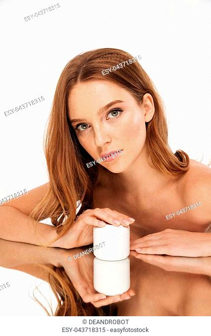 Vertical Beauty portrait of ginger woman with long hair reclines on mirror table while holding bottle of body cream and looking at the camera over grey...