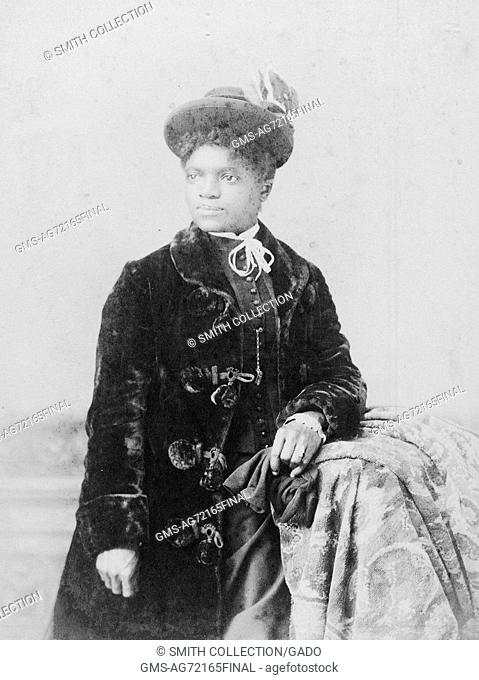 A photographic three-quarter length portrait of an unidentified woman, she is wearing a long, velvet coat and a hat, she leans casually on a tall