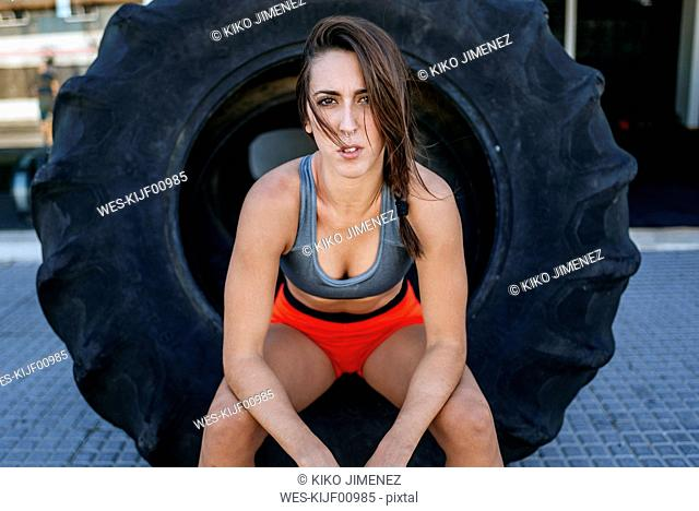 Female athlete sitting in tractor tyre