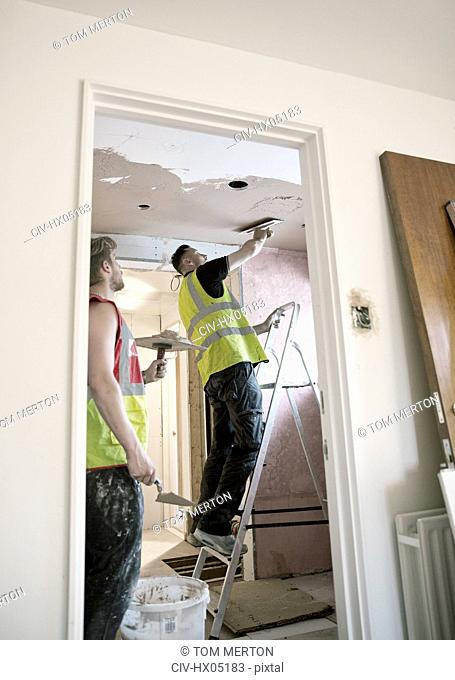 Construction workers plastering ceiling in house