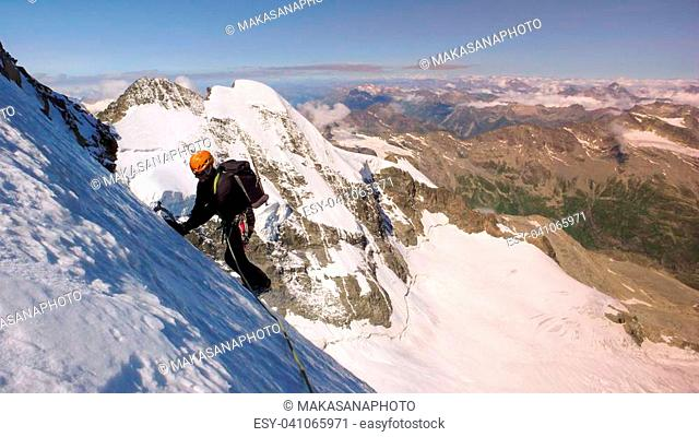 A horizontal view of a male mountain climber on a high alpine glacier with a great view of the fantastic mountain landscape behind him