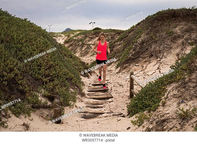 Woman jogging on the boardwalk at beach