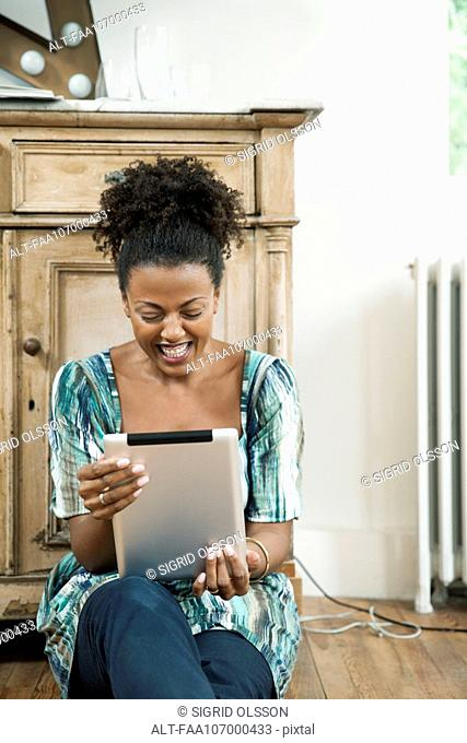 Woman laughing while using digital tablet
