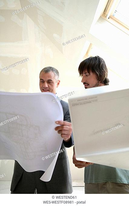 Two men looking at construction plan