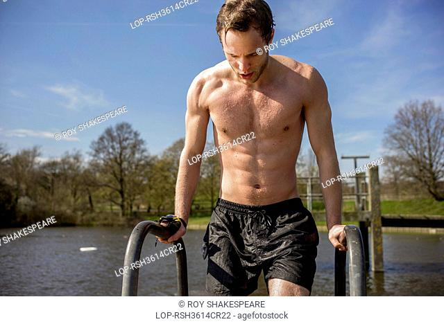 England, London, Hampstead Heath. A young man in swimming trunks next to spring fresh water ponds