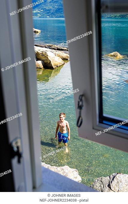 Boy standing in sea seen from the window