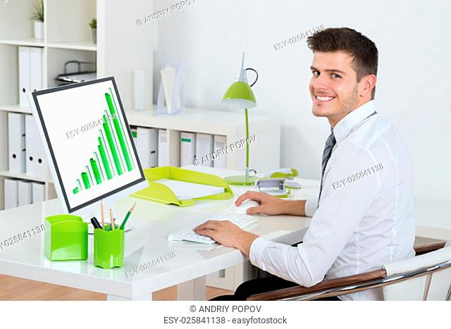 Young Businessman Smiling While Analyzing Graph On Computer In Office