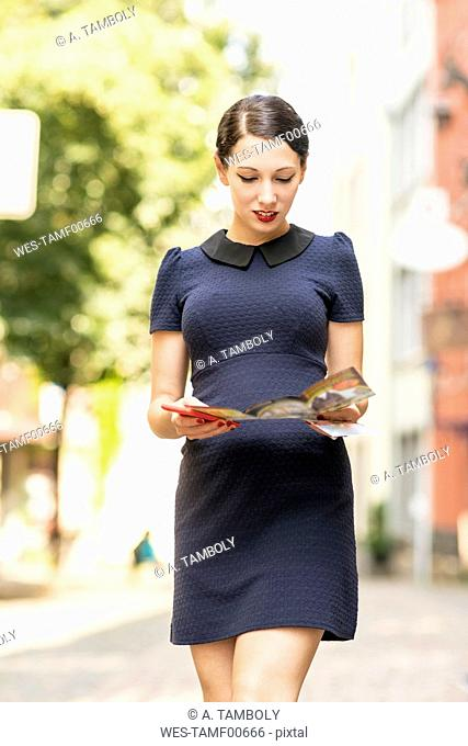 Young woman walking with cell phone and flyer in the city