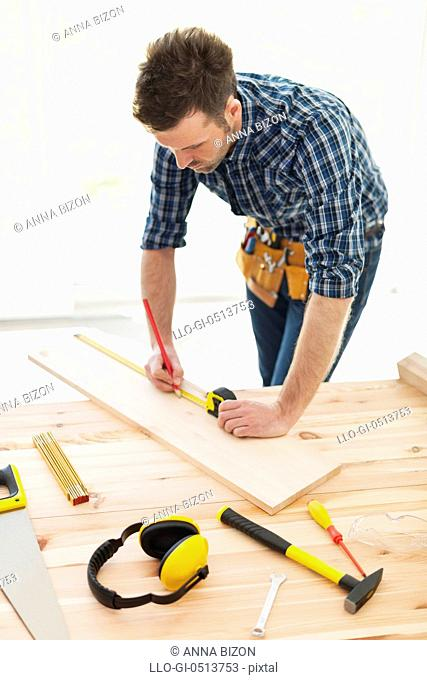 Carpenter checking dimensions of wooden plank. Pilzno, Poland