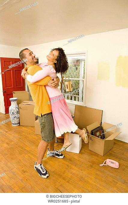 Couple embracing in new home with boxes