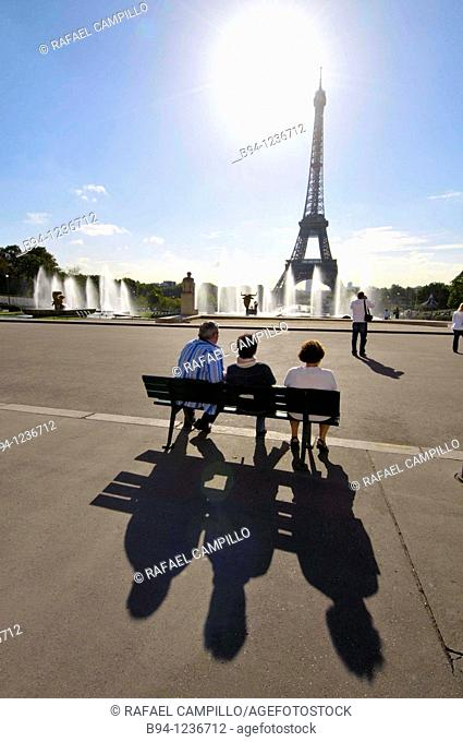 People sitting in the Gardens of the Tocadero. Eiffel Tower and Warsaw Fountain by Roger-Henry Expert. Paris, France
