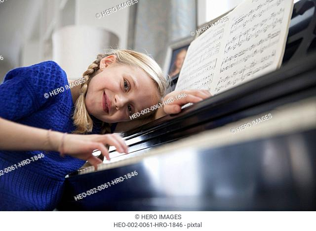 Portrait of young girl playing piano at home