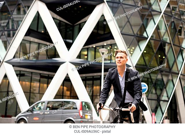 Businessman on bike, 30 St Mary Axe in background, London, UK