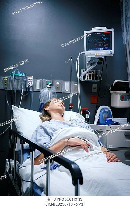 Caucasian girl sleeping in hospital bed