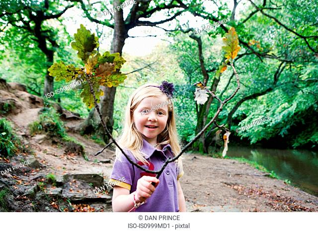 Girl holding an oak branch in a woodland