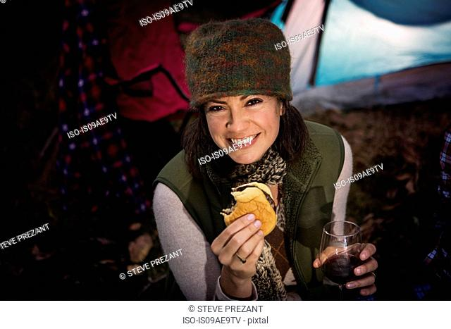 Mature woman holding burger and glass of wine
