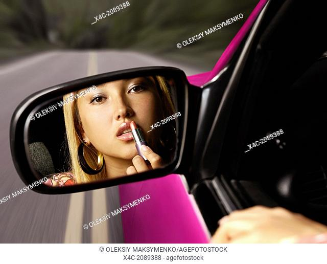 Young pretty asian woman applying lipstick in a car on a highway, looking in a rear view mirror. Distracted driving concept