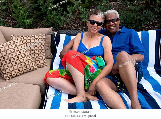 Portrait of senior couple outdoors, relaxing on loungers, smiling