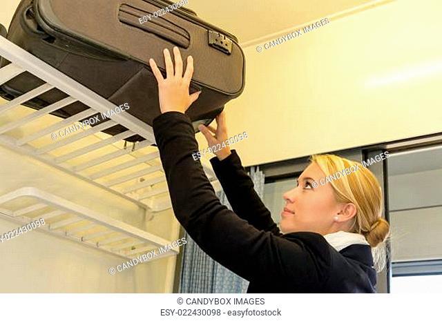 Woman putting her luggage on train rack