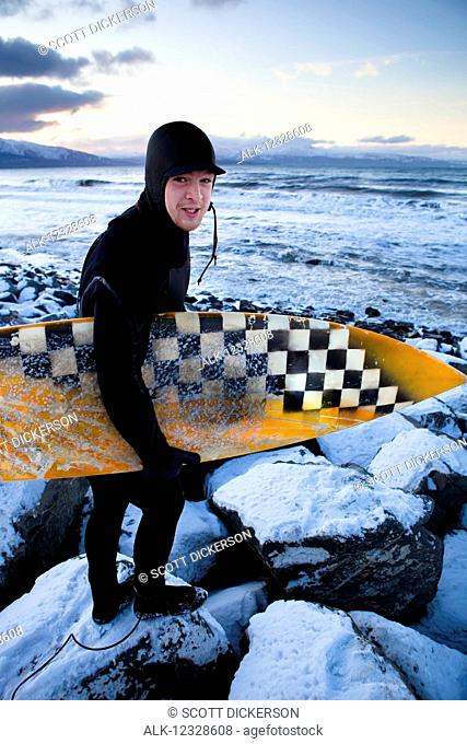Surfer preparing to surf in winter near Homer, South-central Alaska; Alaska, United States of America