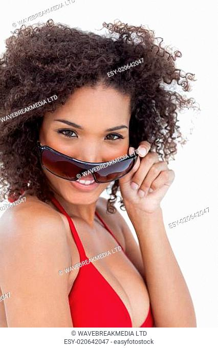 Smiling young woman looking over her sunglasses