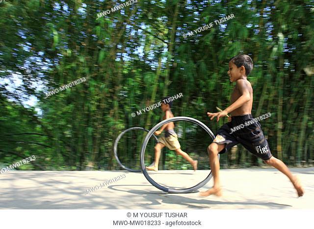 Children running bicycle tires, at a village in Manikganj, Bangladesh October 4, 2008