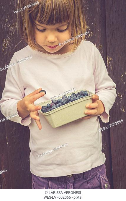 Little girl with box of blueberries