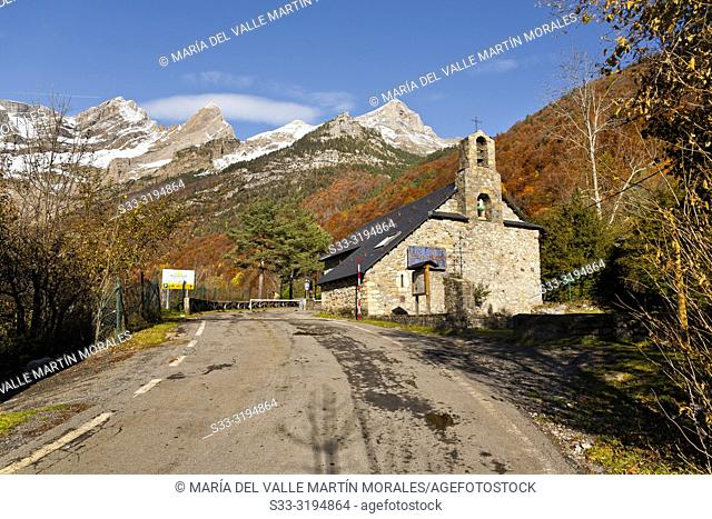 Virgen de Pineta hermitage, road and Pineta Circus on the background in autumn time. Huesca. Aragon. Spain
