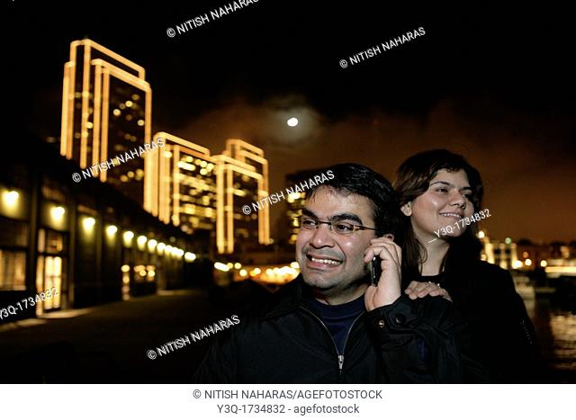 Young Indian couple chatting with family and friends over cell phone while visiting San Francisco, USA
