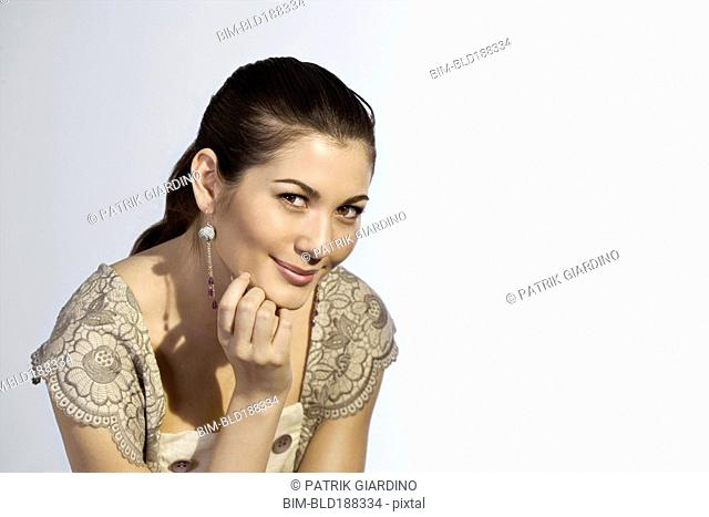 Mixed Race woman resting chin on hand